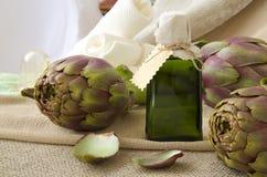 Artichoke oil. A glass bottle of artichoke oil on a sackcloth royalty free stock images