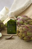 Artichoke oil. A glass bottle of artichoke oil on a sackcloth royalty free stock photos