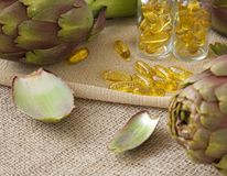 Artichoke oil softgels. On a sackcloth Royalty Free Stock Photo