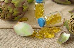 Artichoke oil softgels. On a sackcloth stock photos