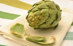 Artichoke salad. Artichoke on a napkin surrounded by a striped tablecloth Stock Photo