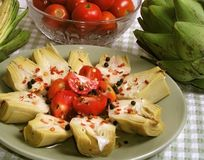 Artichoke Salad. With tomatoes, olive oil, and peppercorns and pepper flakes on green plate. Still life arrangement with bowl of tomatoes and whole artochokes Stock Photography