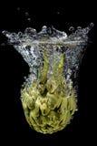 Artichoke splashing into the water royalty free stock images