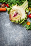 Artichoke and  vegetables ingredients for cooking on gray rustic background, top view. Vegetarian and health food concept. Royalty Free Stock Photos