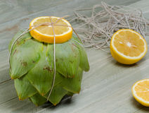 Artichoke with vooking twine and lemon Stock Photos