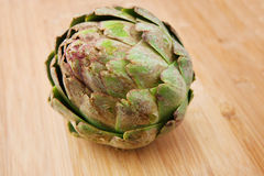 Artichoke on a wooden cutting board Stock Images