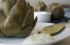 Artichokes. Artichoke on a plate with dip royalty free stock photos