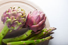 Artichokes and asparagus on a wooden board.  Royalty Free Stock Images