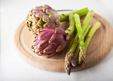 Artichokes and asparagus. On a wooden board Royalty Free Stock Image
