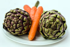 Artichokes and Carrots on a Plate Stock Photos