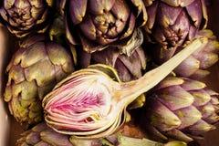 Artichokes. Pile of Purple artichokes ready for cooking. One artichoke is cut Stock Image