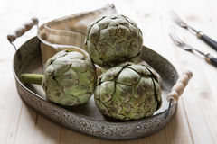 Artichokes on a plate. Three artichokes on an old plate with a napron and two old forks Royalty Free Stock Photography
