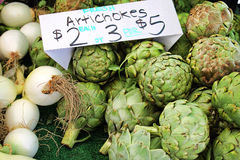 Artichokes for Sale at a Farmer's Market. Pile of freshly picked artichokes and some white onions are under a hand written sign on a table at a farmer's market Royalty Free Stock Photo