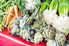 Artichokes, scallions, carrots, beans in a Paris market Royalty Free Stock Images
