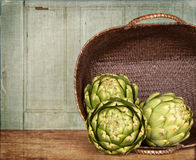 Artichokes spilling out of a basket Stock Photos
