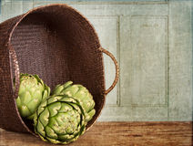 Artichokes spilling out of a basket Royalty Free Stock Photos