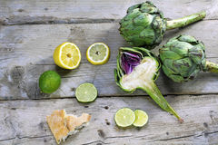 Artichokes whole and halved with lemons, limes and bread on weat Stock Photos