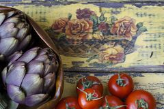 Artichokes in a wooden bowl in a countryside background. Artichokes in a wooden bowl and other ingredients such as tomatoes resting on an ancient yellow shabby Royalty Free Stock Photos