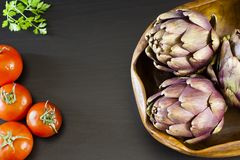 Artichokes in a wooden bowl. With tomatoes and fresh parsley on a brown table Stock Photo