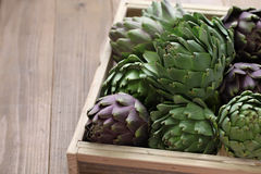 Artichokes in wooden box. On wooden background Royalty Free Stock Photo