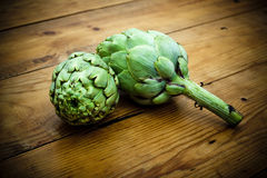 Artichokes on wooden table Stock Photography