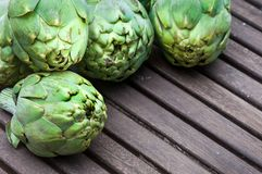 Artichokes on wooden table royalty free stock photography