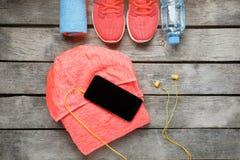 Article de sport et le smartphone avec des écouteurs sur un fond en bois Images libres de droits
