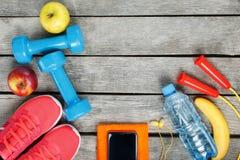 Article de sport et le smartphone avec des écouteurs sur un fond en bois Photos stock