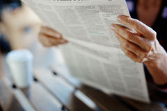 Article in newspaper. Newspaper broadsheet held and read by senior female Stock Photo