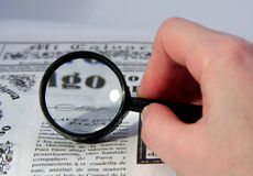 Article reading. In the newspaper by means of increase a magnifier royalty free stock photo