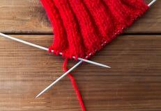 Article tricoté à la main avec des aiguilles de tricotage sur le bois Image stock