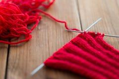 Article tricoté à la main avec des aiguilles de tricotage sur le bois Photos libres de droits