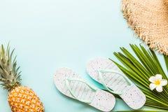 Articles étendus plats de voyage : ananas frais, pantoufles de plage, fleur tropicale et palmette se trouvant sur le fond bleu Pl images stock