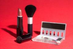 Articles de maquillage sur le fond rouge avec l'éclairage contrasté Image libre de droits