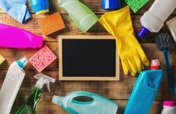 Articles de nettoyage avec le tableau vide sur la table en bois Image stock