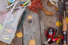 Articles de pêche à bord avec des feuilles d'automne Images stock