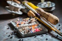 Articles de pêche avec des mouches et des tiges de pêche sur la table en métal Photographie stock libre de droits