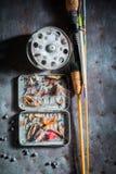 Articles de pêche avec des mouches, des flotteurs et des tiges sur la table en métal Images stock