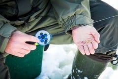 Articles de pêche avec l'amorce dans la main du ` s de pêcheur, pêche d'hiver Photographie stock libre de droits