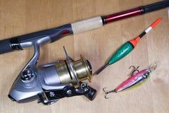 Articles de pêche, bobine, flotteur et amorces sur un fond en bois Photos stock