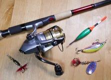 Articles de pêche, bobine, flotteur et amorces sur un fond en bois Photo libre de droits