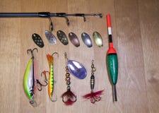 Articles de pêche, différents fileurs pour une amorce des poissons et flotteur sur le fond en bois Images stock