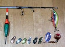 Articles de pêche, différents fileurs pour une amorce des poissons et flotteur sur le fond en bois Images libres de droits
