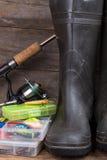 Articles de pêche et bottes en caoutchouc sur le panneau de bois de construction Photographie stock libre de droits