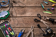Articles de pêche - pêche tournant, ligne de pêche, crochets et attraits sur le fond en bois Image stock