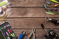 Articles de pêche - pêche tournant, ligne de pêche, crochets et attraits sur le fond en bois Photographie stock