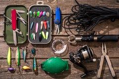 Articles de pêche - pêche tournant, ligne de pêche, crochets et attraits sur le fond en bois Images stock