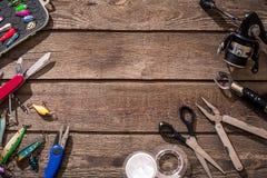 Articles de pêche - pêche tournant, ligne de pêche, crochets et attraits sur le fond en bois Photos stock