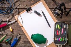 Articles de pêche - pêche tournant, ligne de pêche, crochets et attraits sur le fond en bois Image libre de droits