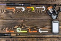 Articles de pêche - pêche tournant, ligne de pêche, crochets, navigateur et bobine sur le fond en bois Images stock